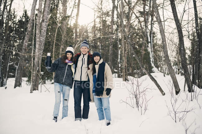 Full length of smiling friends standing against trees on snow covered field — Stock Photo