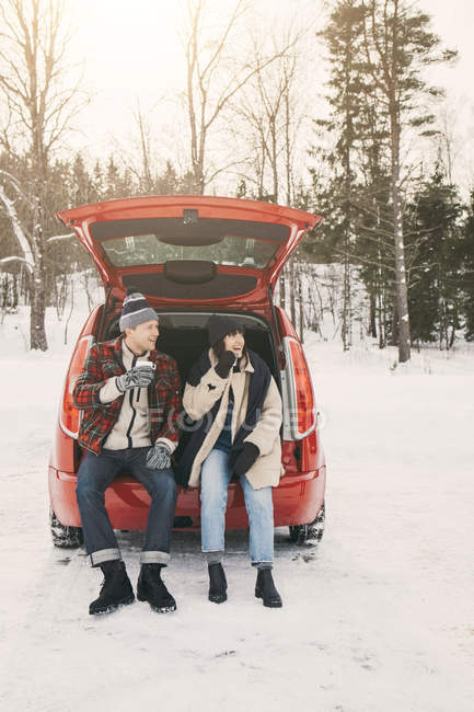 Full length of friends having coffee while sitting in car trunk on snowy field — Stock Photo