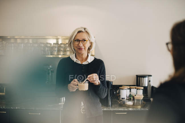 Businesswoman looking at colleague while making tea in office — Foto stock