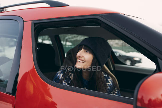 Donna sorridente che osserva via, stando seduti in automobile rossa — Foto stock