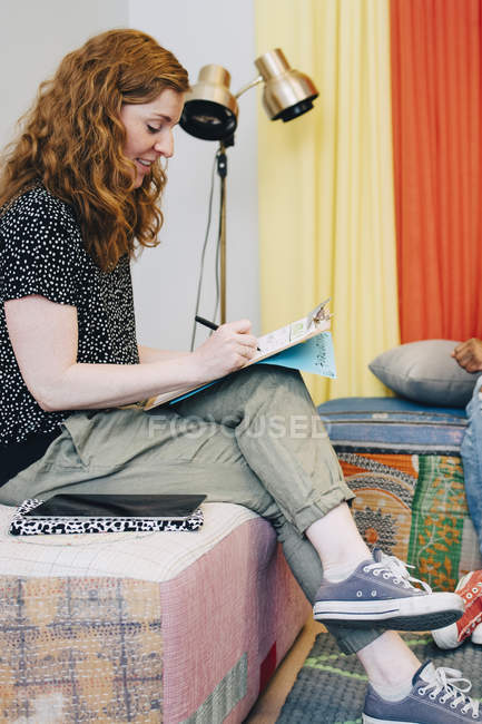 Seitenansicht der rothaarigen Geschäftsfrau, die auf Klemmbrett schreibt, während sie in der Lobby des Kreativbüros sitzt — Stockfoto