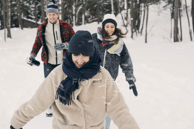 Cheerful friends walking on snow covered field — Stock Photo