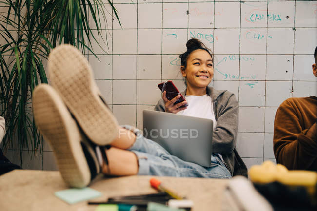 Smiling young businesswoman sitting with feet up on desk using wireless technologies by colleague against wall at office - foto de stock