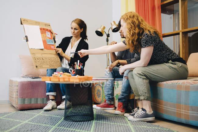 Multiethnische Geschäftskollegen diskutieren Strategie über Plakat, während sie auf dem Sofa in der Lobby des Kreativbüros sitzen — Stockfoto