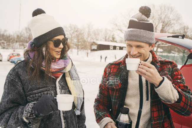 Smiling friends talking while having coffee at snowy park — Stock Photo