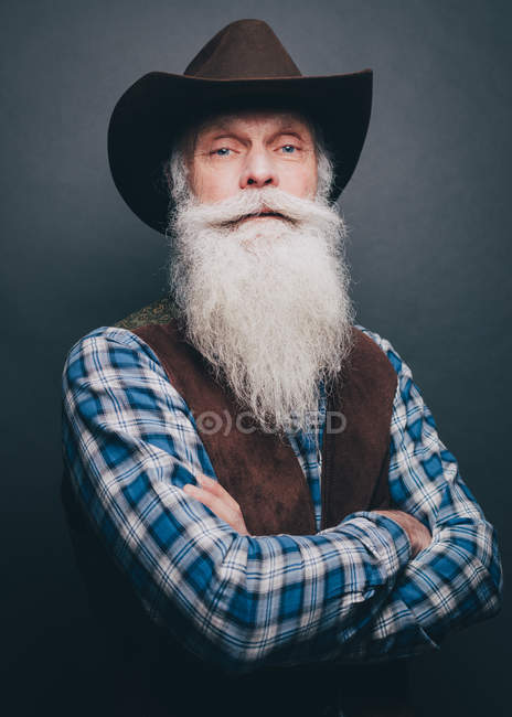 94dcb13ca1b Bearded senior man wearing cowboy hat standing arms crossed against gray  background — Stock Photo