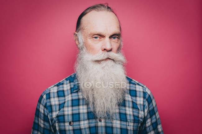 Retrato de hombre mayor serio con larga barba blanca sobre fondo rosa - foto de stock