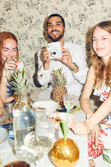 Smiling young man holding camera while sitting amidst female friends at home during dinner party — Stock Photo