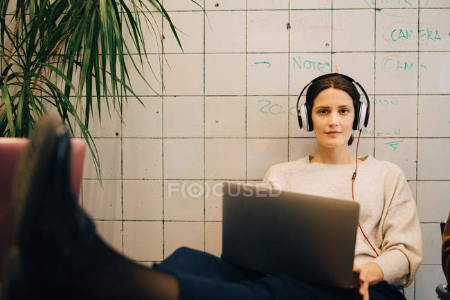 Portrait of confident young female computer hacker listening through headphones while sitting with laptop against tile wall — Stock Photo