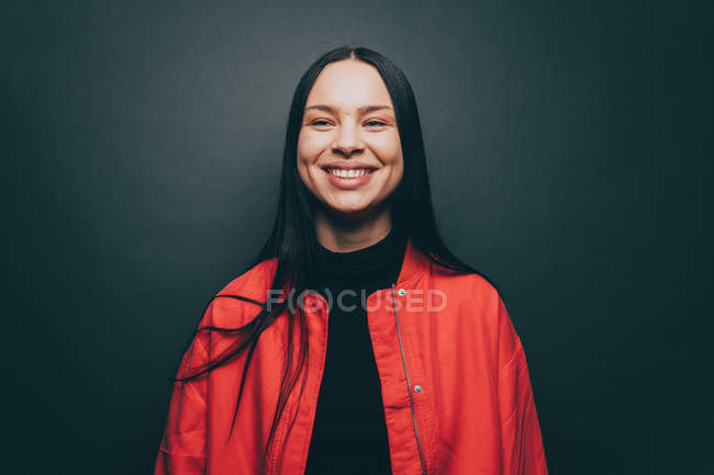 Young woman smiling over gray background — Stock Photo