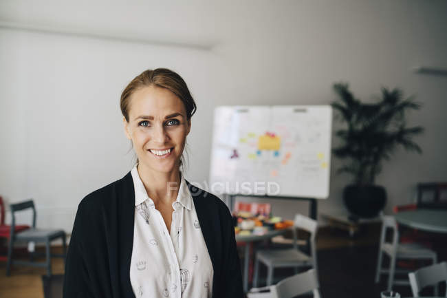 Portrait of smiling mid adult businesswoman standing at creative office — Stock Photo