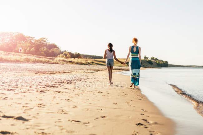 Rückansicht des Mädchens in voller Länge, das sich an der Hand seiner Mutter hält, während es an sonnigen Tagen am Strand spazieren geht — Stockfoto
