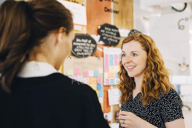 Smiling businesswoman discussing with female colleagues at creative office — Stock Photo