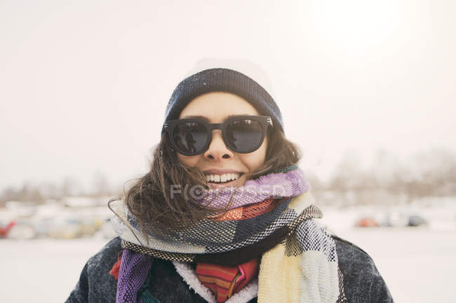 Close-up of smiling woman wearing scarf and sunglasses at park during winter — Stock Photo