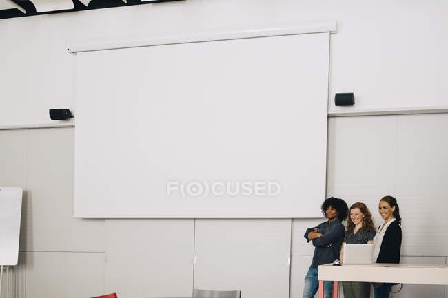 Smiling multi-ethnic technicians standing by blank projection screen at creative office — стоковое фото