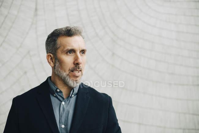 Вдумчивый зрелый бизнесмен против стены в офисе — стоковое фото