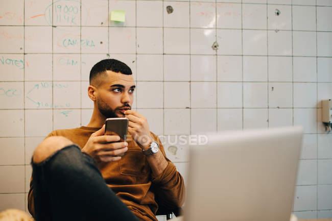 Giovane programmatore maschio guardando lontano mentre seduto con smart phone contro muro in ufficio — Foto stock