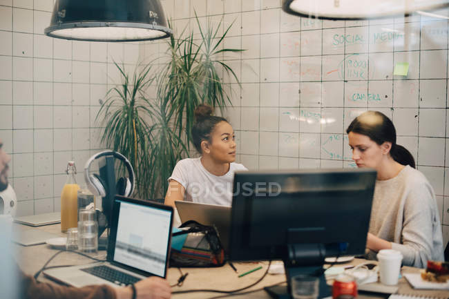 Multi-ethnic female hackers working at desk in creative office seen through window — Stock Photo