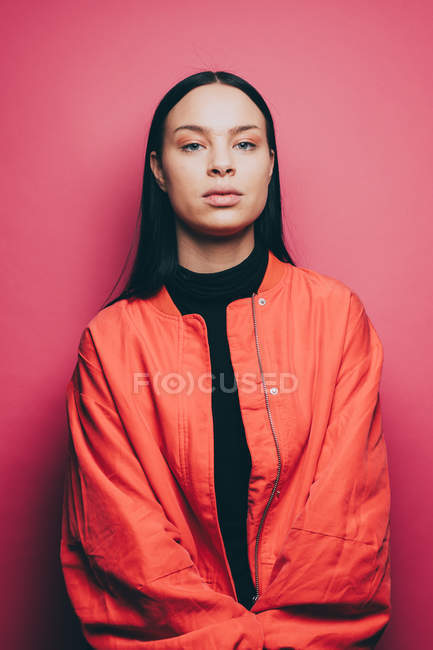 Portrait of confident woman wearing orange jacket over pink background — Stock Photo