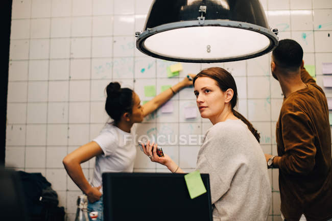 Young businesswoman looking away while hackers planning over wall at small office — Stock Photo