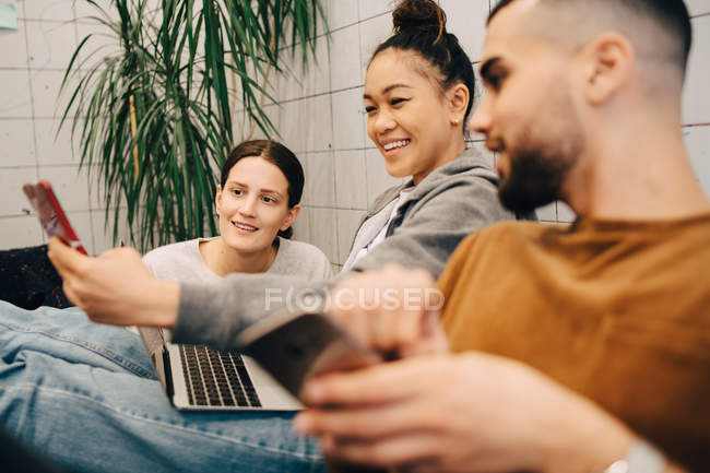 Smiling young businesswoman sharing mobile phone with colleagues while sitting at creative office — Stock Photo