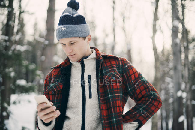 Man using smart phone while standing at park during winter — Stock Photo