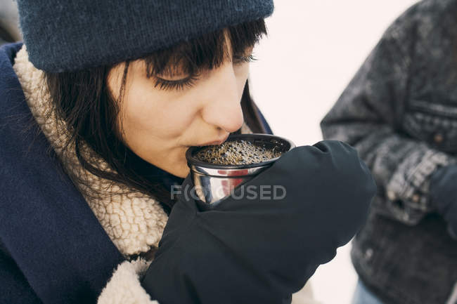 High angle view of woman drinking coffee while standing with friend — Stock Photo