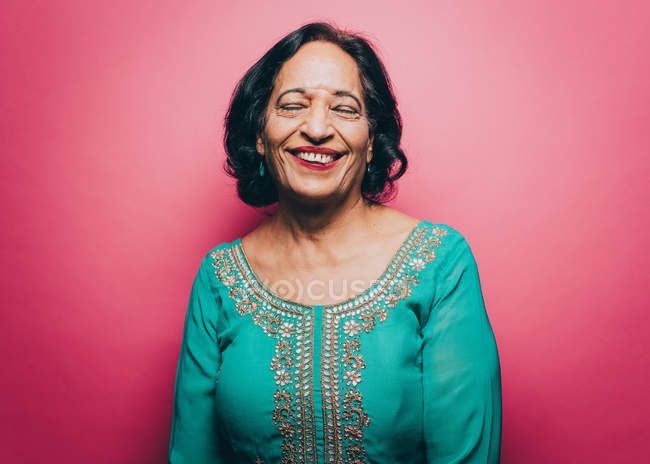 Smiling senior woman with eyes closed over pink background — Stock Photo