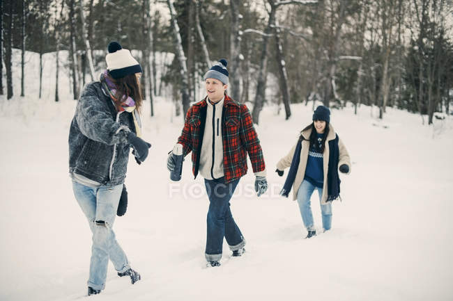 Full length of friends talking while walking on snow covered field — Stock Photo