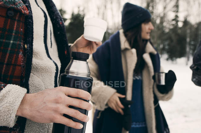 Midsection of man having coffee with friends at park during winter — Stock Photo