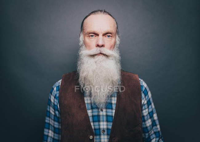 Retrato de hombre confía en senior con larga barba blanca sobre fondo gris - foto de stock