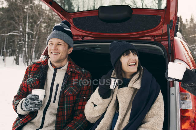 Happy woman having coffee while sitting with friends in car trunk during winter — Stock Photo