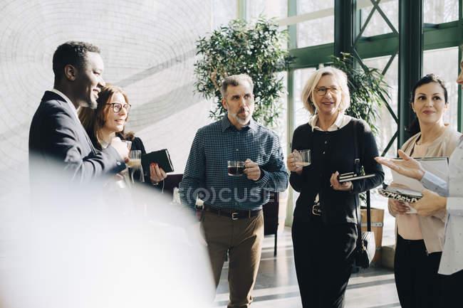 Коллеги слушают деловую женщину за чашечкой кофе в офисе — стоковое фото