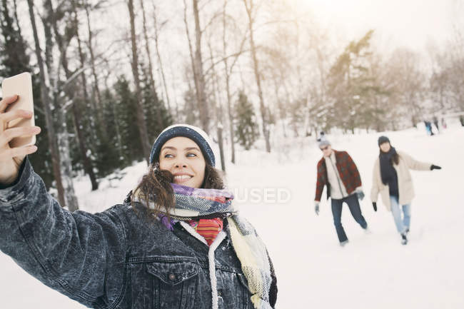 Smiling woman taking selfie while friends walking in background — Stock Photo