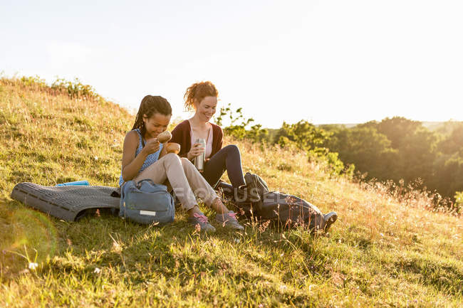 Smiling woman and daughter with insulated drink container sitting on grass at hill against sky during sunset — Stock Photo