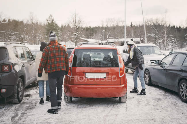 Friends walking towards car at parking lot during winter — Stock Photo