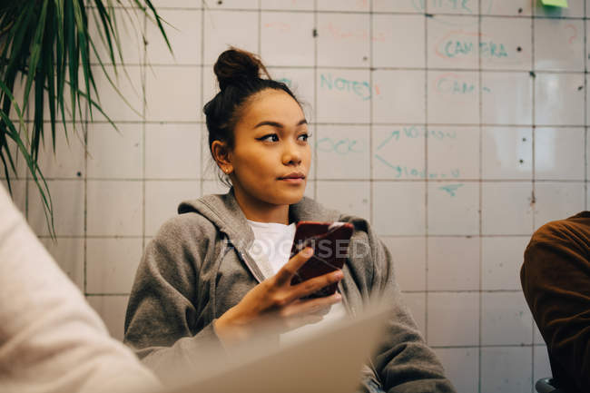 Young female programmer holding smart phone while sitting amidst colleagues against wall at office — Stock Photo