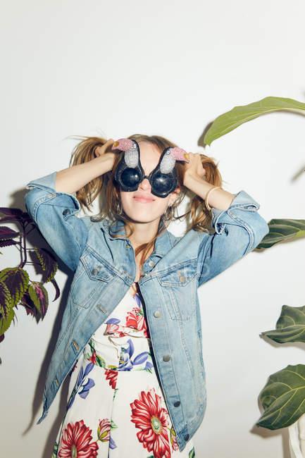 Улыбающаяся молодая женщина с руками в волосах, стоящая среди растений у белой стены дома — стоковое фото