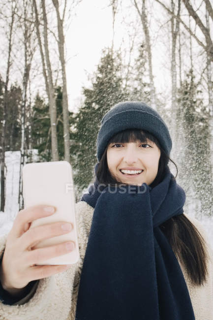 Smiling mid adult woman taking selfie through mobile phone during winter — Stock Photo