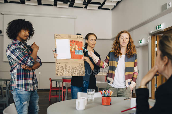Confident businesswoman with colleagues explaining strategy to female manager at creative office — Stock Photo