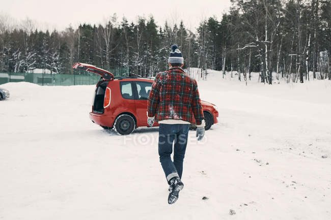 Rear view of man walking towards red car on snow covered landscape — Stock Photo