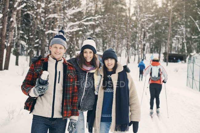 Portrait of smiling friends standing on snow covered field at park — Stock Photo