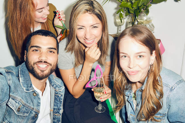 Portrait of smiling young multi-ethnic friends enjoying party at apartment — Stock Photo
