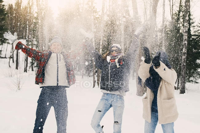 Playful friends throwing snow while standing on field at park — Stock Photo