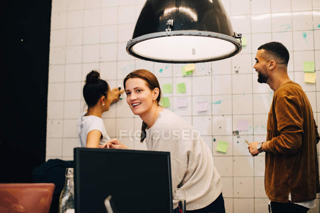 Smiling young businesswoman looking away while hackers planning over wall at small office — Stock Photo