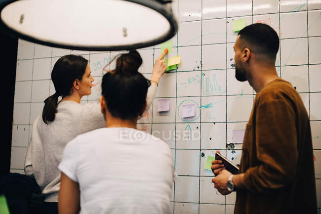 Young female computer programmer explaining strategy on wall to multi-ethnic colleagues at small creative office - foto de stock