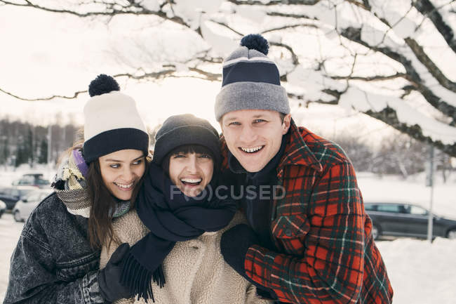 Cheerful friends in warm clothing embracing at park during winter — Stock Photo