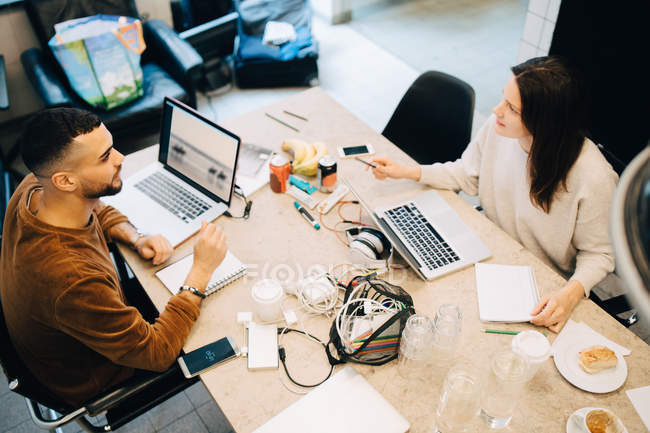 High angle view of male and female programmers discussing while sitting at desk in creative office — Stock Photo