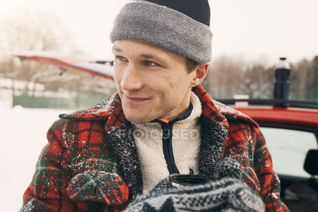 Close-up of thoughtful smiling man having coffee against car — Stock Photo