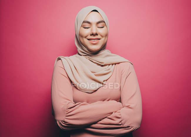 Улыбаясь мусульманская женщина с глазами закрыты восстали против розовый фон — стоковое фото